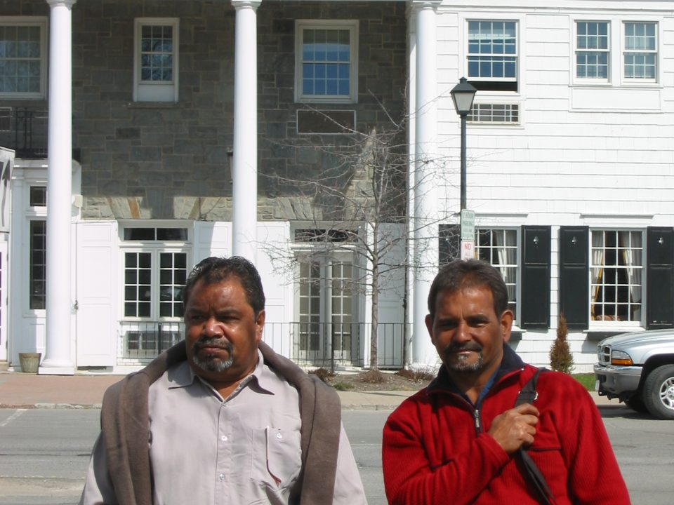 Ezzard Flowers and Athol Farmer (right) standing outside the Colgate University Guesthouse where they and John Stanton stayed when visiting Colgate University, Hamilton, New York State, 13th April 2005. Photograph taken by John Stanton. Berndt Museum of Anthropology, University of Western Australia.