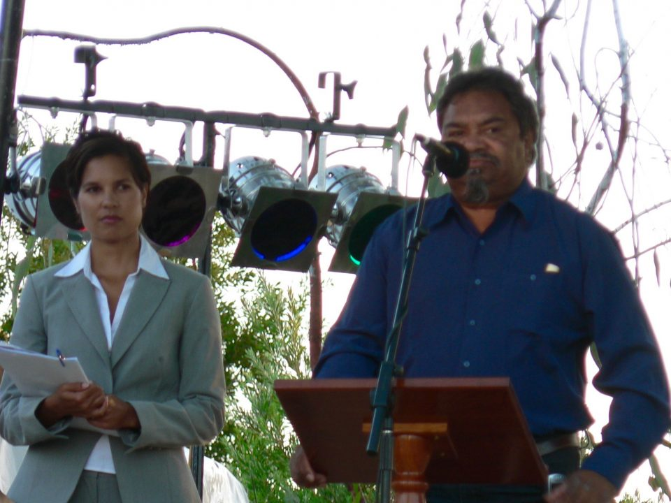 Ezzard Flowers speaking at the Official Opening of Koorah Coolingah exhibition, Katanning, with MC Norelle Jacobs in the background, 24th February 2006. Berndt Museum of Anthropology, The University of Western Australia.