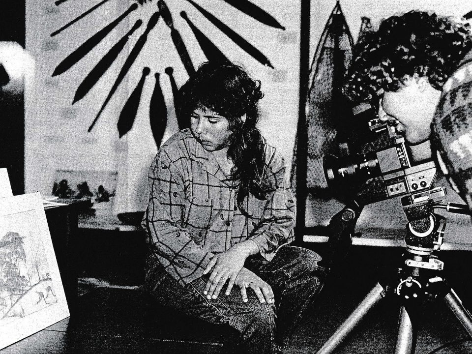 Trainees Tina Hansen (left) and Cora Farmer (right) videotape one of the early examples of Carrolup children's art held in the Berndt Museum for a film that was being made by John Stanton for the Marribank Community. Uniview, The University of Western Australia, 5/4, pp. 1-2, July 1986.