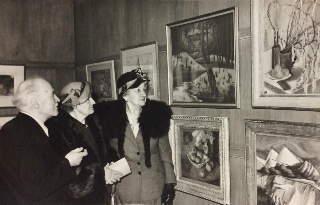 Parnell Dempster's Down to Drink adorns a wall at the 45th Annual Exhibition of the Pastel Society in London, 1951. Mrs Rutter proudly discusses the drawing with Mr and Mrs Richter. Mary Durack Miller Collection, J. S. Battye Library of West Australian History, 1951.