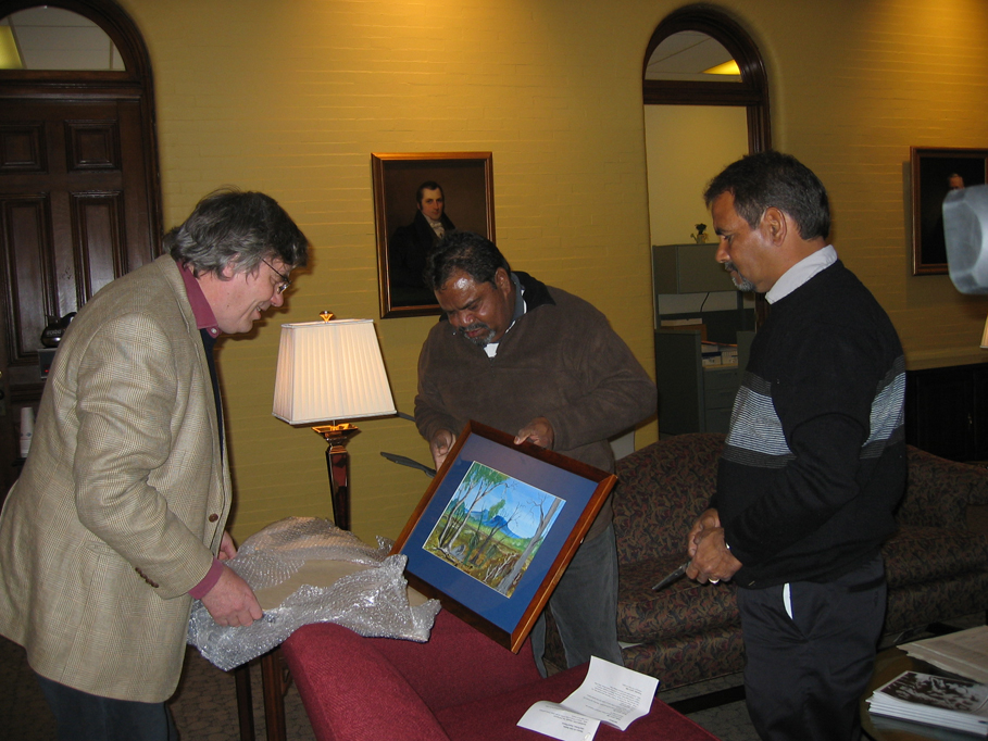 Howard Morphy and Ezzard Flowers inspect the painting that Athol Farmer brought from Katanning to give to the President of Colgate University, Rebecca Chopp.