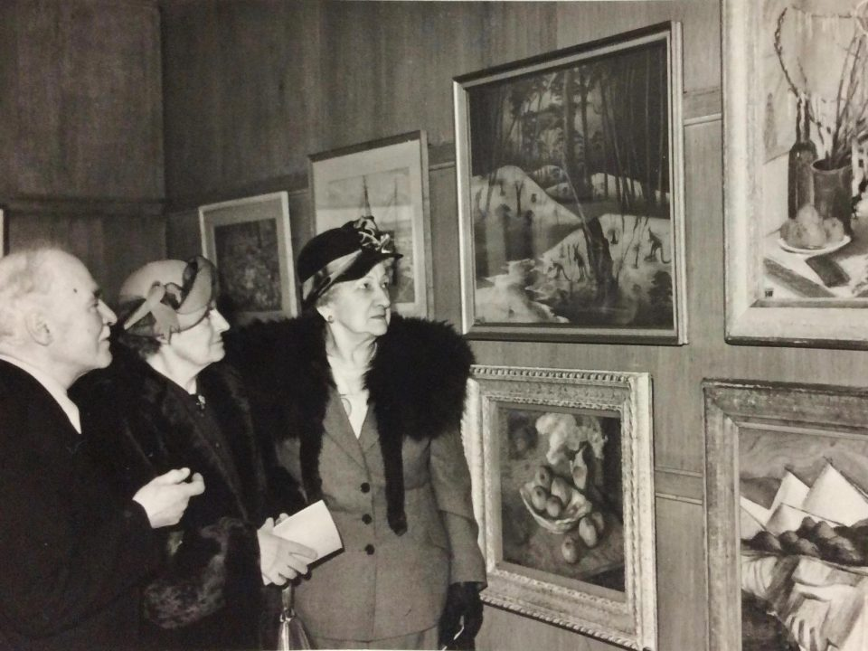 A pastel by Parnell Dempster adorns a wall at the Pastel Society in London in 1951, proudly talked about by Mrs. Rutter.