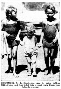 COMPANIONS: At the Swanbourne camp for native children Mildred Jones and Joan Indich take a small white friend, Jane Heller, for a swim. The West Australian, 19th January 1949.