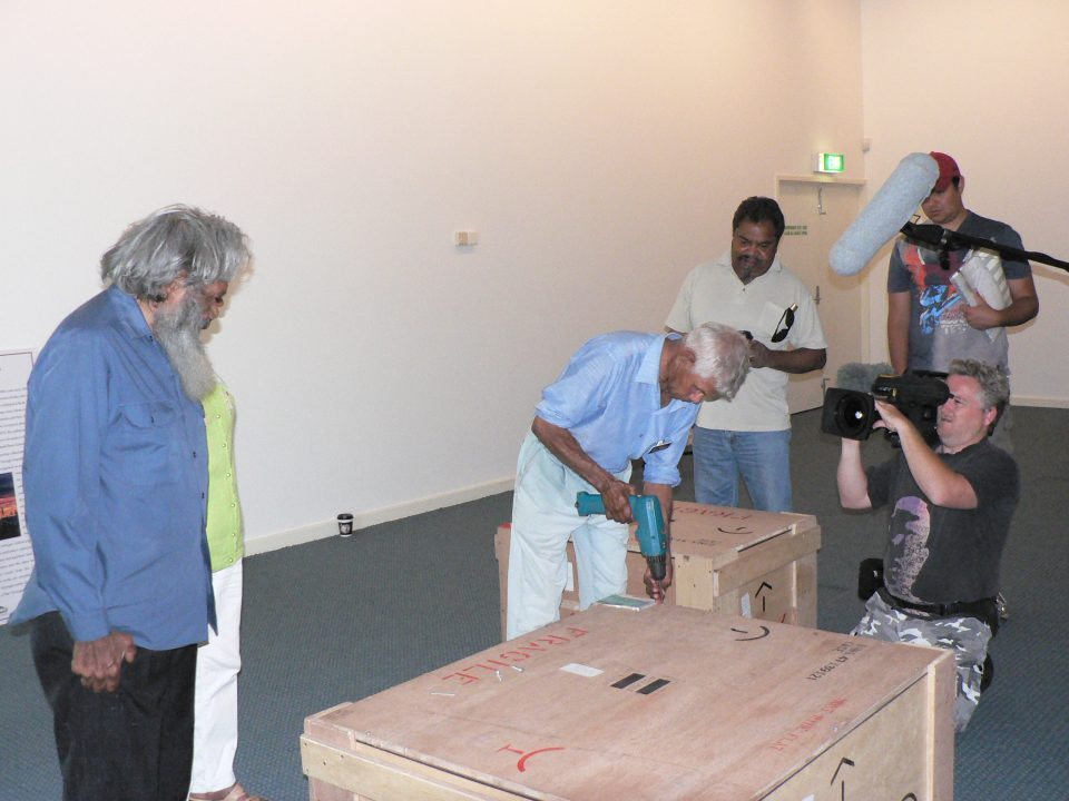 Angus Wallam (Centre) unscrews the first crate of works from Colgate University, as Milton Jackson (Far Left) and Ezzard Flowers (Mid Right) look on. The ABC's Message Stick program records the moment. Photograph by John Stanton, 27th February 2006. Courtesy of Berndt Museum of Anthropology, The University of Western Australia.
